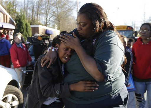 a-woman-comforts-a-child-after-after-a-shooting-at-an-price-middle-school-in-atlanta-thursday-jan-31-2013-a-14-year-old-boy-was-wounded-outside-the-school-thursday-afternoon-and-a-fellow-student-was-in-custody-as-a-suspect-authorities-said-no-other-students-were-hurt