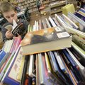 Jayden Swartz, 10, a third-grader, flips through a book Wednesday while looking for three books to c...