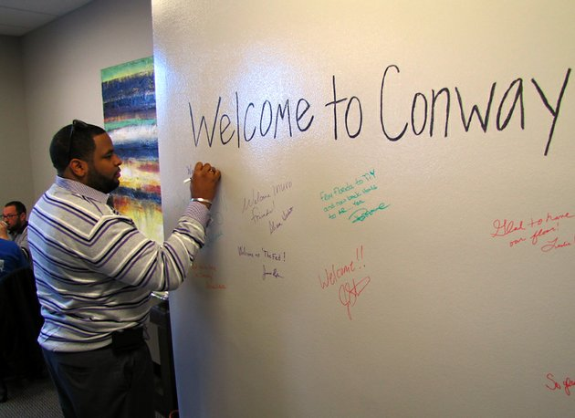 korry-garrett-signs-a-wall-at-the-announcement-thursday-jan-31-2013-that-internet-marketing-and-technology-firm-inuvo-is-moving-to-conway