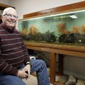 Denny Rogers sits in his favorite personal space, one of the aquarium rooms he has set up at his hom...