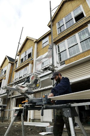 A builder works on condominiums in North Andover, Mass. Spending on construction projects rose to $885 billion in December, the Commerce Department said Friday.