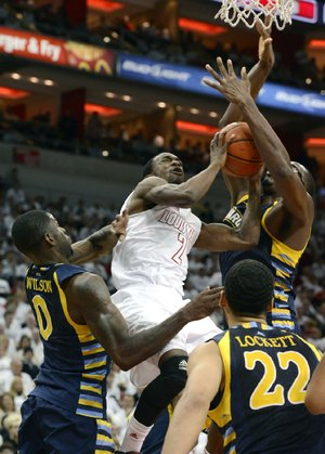 Louisville guard Russ Smith (2) fights his way to the basket past Marquette's Trent Lockett (22) and Derrick Wilson during the second half of Sunday's game in Louisville, Ky. Smith finished with 18 points and Louisville defeated Marquette 70-51.