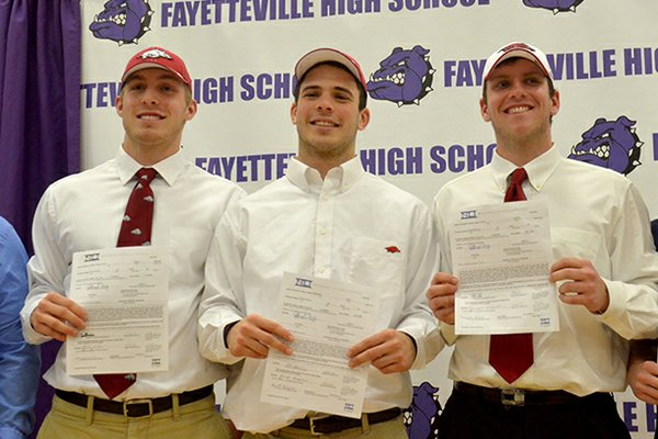 Fayetteville High students (left to right) Brooks Ellis, Alex Brignoni and Austin Allen get ready to pose for a group photo after they signed their letters of intent to play football at the University of Arkansas during the official ceremony Wednesday afternoon.