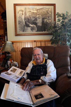 J.D. Fletcher of Eagle Rock, Mo., has 40 to 50 albums of photos, letters and newspaper and magazine articles from his years as a fishing guide on Table Rock Lake and the Kings River. He's kept every photo he's taken since the 1950s and has a vast collection of lures and fishing tackle. Here he looks at some of his photos on Feb. 1. The photo above Fletcher's chair shows Fletcher, second from left, and some of his friends after trout fishing at Roaring River State Park.