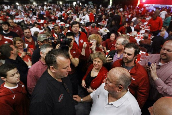 Arkansas Coach Bret Bielema (left) talks with Dennis Welch on Thursday during the Signing Day in the Rock event at Verizon Arena in North Little Rock.