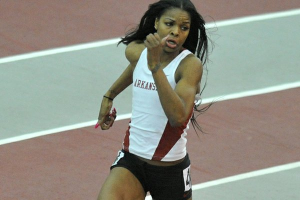 University of Arkansas runner Regina George runs the final turn in the women's 400 M Invitational at the Tyson Invitational track meet at the Randal Tyson Track Complex in Fayetteville.