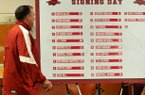 University of Arkansas head football coach Bret Bielema walks past the signing day list of 22 players who committed to the Razorbacks as he begins the press conference Wednesday afternoon in Fayetteville.