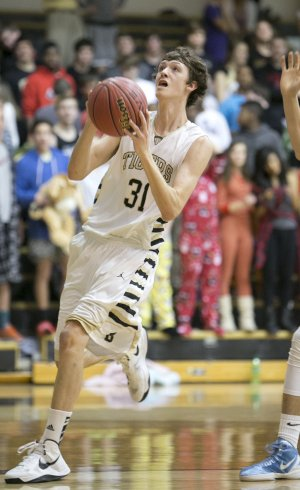 Aaron Ward of Bentonville drives to the basket on Feb. 5 during the Tigers game against Springdale Har-Ber at Bentonville.