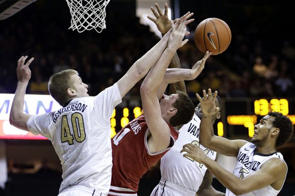 Arkansas forward Hunter Mickelson, second from left, loses the ball as he tries to shoot among Vanderbilt defenders Josh Henderson (40), Dai-Jon Parker (24) and Kevin Bright, right, during the first half of an NCAA college basketball game on Saturday, Feb. 9, 2013, in Nashville, Tenn. (AP Photo/Mark Humphrey)