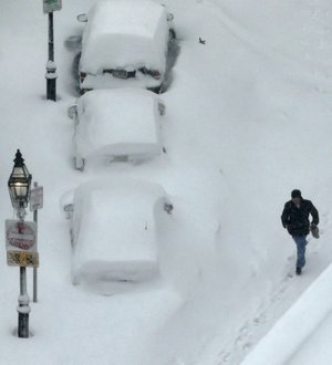 A man walks past snow covered cars in the South End neighborhood of Boston, Saturday, Feb. 9, 2013. The Boston area received about two feet of snow from a winter storm.