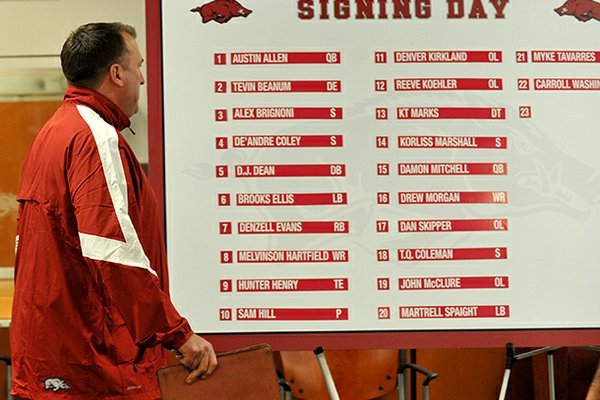 Arkansas head football coach Bret Bielema walks past the signing day list of players who committed to the Razorbacks at a press conference in Fayetteville.
