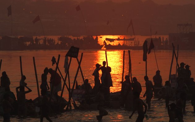hindu-devotees-pray-against-a-setting-sun-after-a-holy-dip-at-sangam-the-confluence-of-hindu-holy-rivers-ganges-yamuna-and-the-mythical-saraswati-during-the-maha-kumbh-festival-at-allahabad-india-sunday-feb-10-2013-led-by-heads-of-monasteries-arriving-on-chariots-and-ash-smeared-naked-ascetics-millions-of-devout-hindus-plunged-into-the-frigid-waters-of-the-holy-ganges-river-in-india-on-sunday-in-a-ritual-that-they-believe-will-wash-away-their-sins-sunday-was-the-third-of-six-auspicious-bathing-days-during-the-kumbh-mela-or-pitcher-festival-which-lasts-55-days-and-is-one-of-the-worlds-largest-religious-gatherings