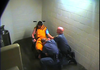 A frame from a video showing Benton County jailers restraining and pepper-spraying an inmate.