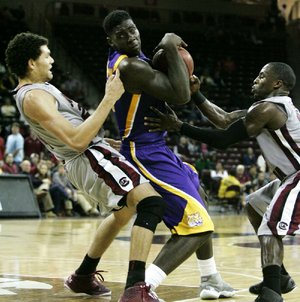 LSU's Johnny O'Bryant (center) drives to the basket against South Carolina's Michael Carrera (left) and Bruce Ellington during the second half of the Tigers' 64-46 victory over the Gamecocks on Thursday in Columbia, S.C. O'Bryant had a career-high 30 points and 10 rebounds for the Tigers.