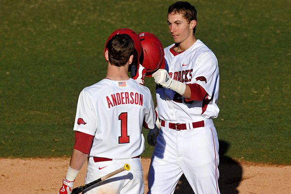 Arkansas first baseman Eric Fisher is greeted by teammate Brian Anderson as he crosses home plate after a solo home run in the third inning of Friday afternoon's season opener at Baum Stadium in Fayetteville.