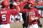Arkansas' Joe Serrano (10) is congratulated at the plate by Brett McAfee after scoring a run and recording and RBI Saturday, Feb. 16, 2013, during the sixth inning of the Hogs' win over Western Illinois at Baum Stadium in Fayetteville.