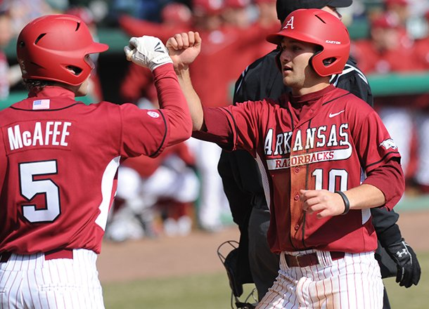 arkansas-joe-serrano-10-is-congratulated-at-the-plate-by-brett-mcafee-after-scoring-a-run-and-recording-and-rbi-saturday-feb-16-2013-during-the-sixth-inning-of-the-hogs-win-over-western-illinois-at-baum-stadium-in-fayetteville