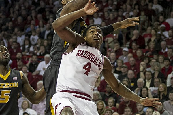Missouri's Alex Oriakhi, top, attempts to rebound against Arkansas' Coty Clarke (4) during the second half an NCAA college basketball game in Fayetteville, Ark., Saturday Feb. 16, 2013. Arkansas defeated Missouri 73-71. (AP Photo/Gareth Patterson)