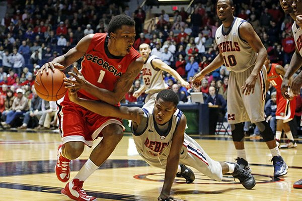 Mississippi guard Jarvis Summers (32) tries to steal the ball from Georgia guard Kentavious Caldwell-Pope (1) in the second half of their NCAA college basketball game in Oxford, Miss., Saturday, Feb. 16, 2013. Mississippi won 84-74. (AP Photo/Rogelio V. Solis)