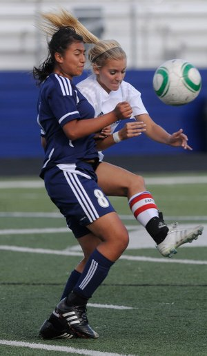 Springdale Har-Ber's Ana Martinez, left, fights for the ball with Rogers High's Kate Schmandt last year at Mountie Stadium in Rogers. The Lady Wildcats will open its 2013 season on Tuesday against Bentonville at Jarrell Williams Bulldog Stadium in Springdale.