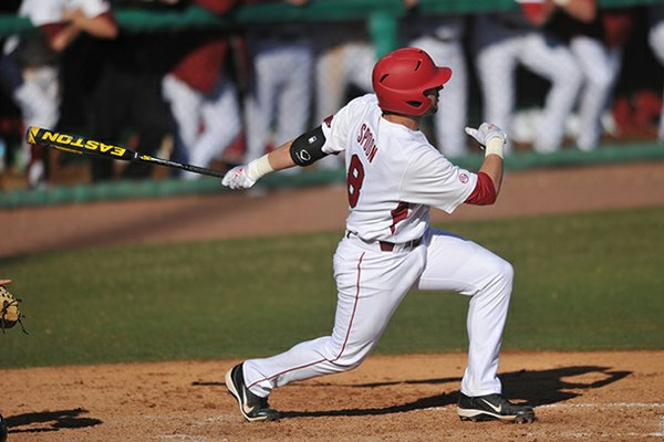 Arkansas batter Tyler Spoon puts the ball into play during his at bat in the sixth inning of the first game in Tuesday afternoon's doubleheader against New Orleans at Baum Stadium in Fayetteville.