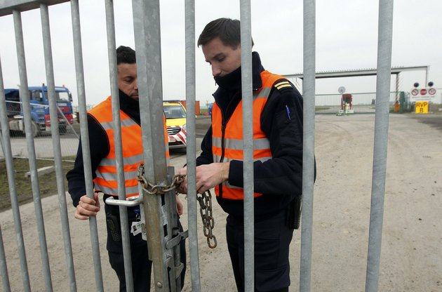two-airport-police-officers-use-a-chain-to-lock-a-gate-which-leads-to-the-airport-tarmac-at-brussels-international-airport-tuesday-feb-19-2013-eight-masked-gunmen-made-a-hole-in-a-security-fence-at-brussels-international-airport-drove-onto-the-tarmac-and-snatched-some-50-million-worth-of-diamonds-from-the-hold-of-a-swiss-bound-plane-without-firing-a-shot-authorities-said-tuesday