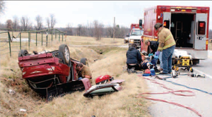 Emergency responders work with one patient injured in a single vehicle rollover accident on Arkansas Highway 72, approximately 4 1/2 miles east of Arkansas 59, on the morning of Feb. 12. Rescuers also work to free a second patient still inside the car.