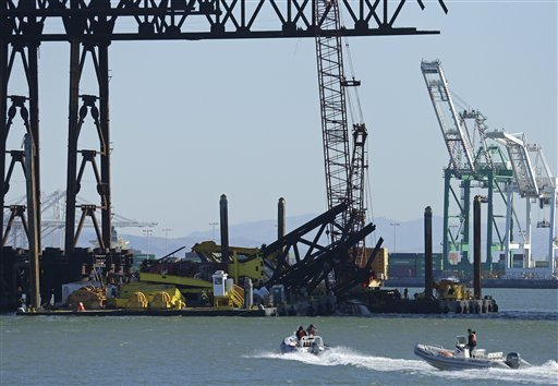 investigators-approach-the-scene-where-a-crane-overturned-onto-a-barge-and-into-san-francisco-bay-seen-from-clipper-cove-on-treasure-island-thursday-feb-21-2013-in-san-francisco-a-crane-tipped-over-while-working-on-the-new-eastern-span-of-the-san-francisco-oakland-bay-bridge-on-thursday-afternoon-but-there-were-no-injuries-and-nothing-leaked-into-the-bay-authorities-said-the-crane-was-on-a-barge-underneath-the-new-span-helping-to-remove-a-temporary-support-structure-and-was-holding-a-piece-of-the-structure-when-it-fell-around-noon-thursday-according-to-bridge-spokesman-andrew-gordon-gordon-said-officials-are-investigating-what-caused-the-crane-to-tip-over-and-whether-the-new-span-was-damaged-at-all-the-new-bridge-is-expected-to-open-over-labor-day-weekend-it-will-connect-oakland-to-treasure-island-and-replace-the-eastern-span-that-was-damaged-during-the-1989-loma-prieta-earthquake