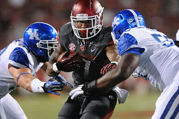 Arkansas running back Knile Davis carries the ball as Kentucky defensive lineman Mike Douglas, right, closes in to make the tackle during the second quarter of play Saturday, Oct. 13, 2012, at Razorback Stadium in Fayetteville.