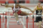 Arkansas senior Caleb Cross clears the final hurdle on his way to a second-place finish ahead of Missouri junior Andy Schuckenbrock in a preliminary heat of the 60-meter hurdles Saturday, Feb. 23, 2013, during the Southeastern Conference Indoor Track and Field Championships at the Randal Tyson Track Center in Fayetteville.