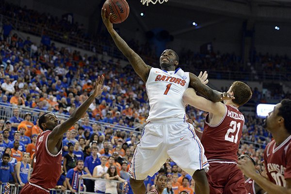 Florida guard Kenny Boynton (1) goes to the basket as Arkansas guard Mardracus Wade (1) and forward Hunter Mickelson (21) defend during the first half of an NCAA college basketball game in Gainesville, Fla., Saturday, Feb. 23, 2013. (AP Photo/Phil Sandlin)