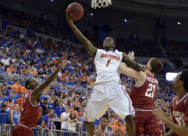 florida-guard-kenny-boynton-1-goes-to-the-basket-as-arkansas-guard-mardracus-wade-1-and-forward-hunter-mickelson-21-defend-during-the-first-half-of-an-ncaa-college-basketball-game-in-gainesville-fla-saturday-feb-23-2013-ap-photophil-sandlin