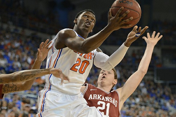 Florida's Erik Murphy (33) tries to block Arkansas guard Michael Qualls (24) as he struggles under the basket during the first half of an NCAA college basketball game in Gainesville, Fla., Saturday, Feb. 23, 2013. (AP Photo/Phil Sandlin)