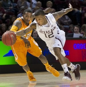 Texas A&M guard Fabyon Harris (12) drives past Tennessee guard Jordan McRae during the first half of Saturday's game in College Station, Texas. Tennessee won 93-85 in four overtimes.