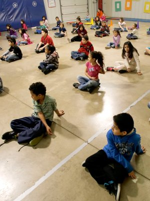 Second-graders in Josh Hicklin's physical education class stretch Monday morning in the gym at Elmdale Elementary School in Springdale. The school has received a $10,000 grant from Lowe's to install a new floor and padding in its gym to make it safer for the kids.