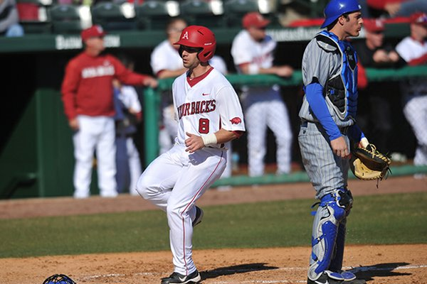 Arkansas outfielder Tyler Spoon scores a run in the first game of a Feb. 19 doubleheader against New Orleans at Baum Stadium in Fayetteville.