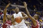 LSU's Anthony Hickey (1) splits Arkansas defenders B.J. Young (11) and Marshawn Powell (33) for a shot during an NCAA basketball game, Wednesday, Feb. 27, 2013, in Baton Rouge, La. LSU won 65-60. (AP Photo/The Advocate, Heather McClelland)