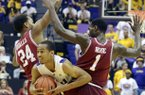 LSU's Charles Carmouche (00) is sandwiched between Arkansas' Michael Qualls (24) and Mardracus Wade (1) during their NCAA college basketball game, Wednesday, Feb. 27, 2013, in Baton Rouge, La. LSU won 65-60. (AP Photo/The Advocate, Heather McClelland)