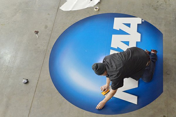 Robbie Hanner with The Sign Factory in Fayetteville, works on preparing an NCAA sign to hang up at the Tyson Indoor Track Facility. Arkansas hosted the 2013 NCAA Track and Field championships.