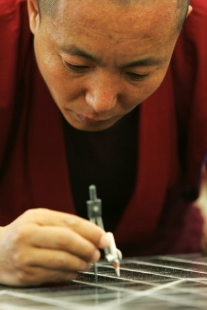 Namgyan Sangpo, a Tibetan monk, works on a mandala at the University of Arkansas at Fayetteville. Mandalas are intricate designs made of colored sand.