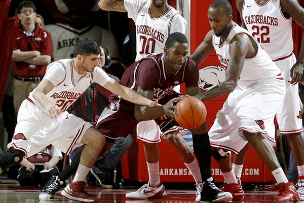 Arkansas juniors Kikko Haydar (left) and Marshawn Powell pressure Texas A&M senior Ray Turner during the first half on Saturday, March 9, 2013, at Bud Walton Arena in Fayetteville.