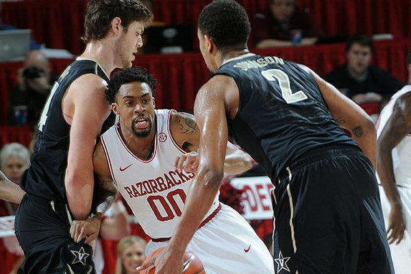 Arkansas' Rashad Madden, center, keeps close to Kedren Johnson of Vanderbilt Saturday, Jan. 12, 2013, during the first half of the first home conference game at Bud Walton Arena in Fayetteville.