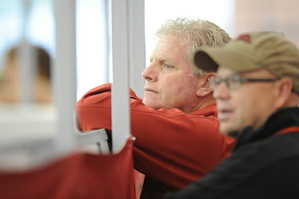 Arkansas coach Chris Bucknam, left, and assistant Danny Greene watch Saturday, Jan. 26, 2013, during the Razorback Invitational at the Randal Tyson Track Center in Fayetteville.