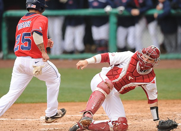 ole-miss-third-baseman-andrew-mistone-scores-as-arkansas-catcher-jake-wise-loses-the-throw-from-the-field-sunday-march-17-2013-during-the-fourth-inning-of-play-against-arkansas-at-baum-stadium