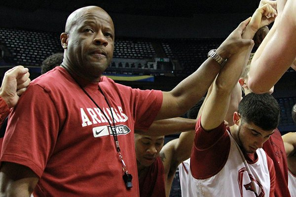 Arkansas basketball coach Mike Anderson joins his team in a prayer after a practice in Nashville on Wednesday as they prepare for the SEC Tournament.