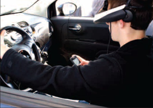 Derek Pruitt uses his cell phone in the driving-while-texting simulator which was at Gravette High School before spring break.