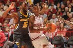 Arkansas sophomore guard BJ Young, right, drives along the baseline as Missouri senior Keion Bell defends Saturday, Feb. 16, 2013, during the first half of play in Bud Walton Arena in Fayetteville.