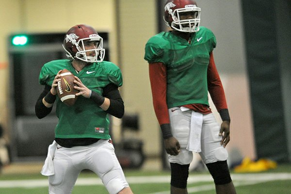 Arkansas quarterback Brandon Allen (left) and Brandon Mitchell warm up as the Razorbacks get ready for Saturday morning's scrimmage in the Pat Walker Pavilion.