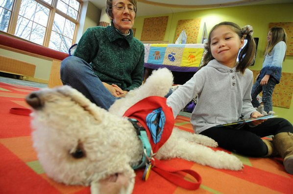 Phoebe Drinkard, 7, right, pets ...