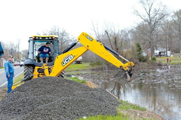 mayflower-street-superintendent-jimmy-johnson-left-oversees-mayflower-water-department-employee-brad-lawrence-as-he-works-friday-on-a-retention-pond-on-highway-89-in-mayflower-following-a-nearby-crude-oil-spill-culverts-were-plugged-to-keep-oil-from-entering-lake-conway-and-dikes-were-built-friday-shortly-after-authorities-were-alerted-to-an-exxon-mobil-underground-pipeline-that-ruptured-at-shade-tree-lane-and-north-starlite-road-in-the-northwoods-subdivision-less-than-a-mile-from-lake-conway-faulkner-county-judge-allen-dodson-said-workers-are-vacuuming-water-and-oil-from-ditches-and-yards-and-placing-the-mixture-into-frac-tanks